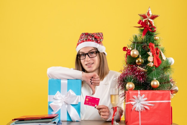Front view female doctor holding present and bank card