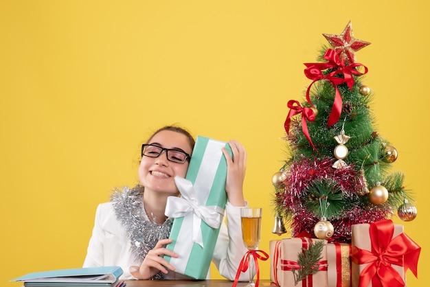 青いパッケージでプレゼントを保持している正面図の女性医師