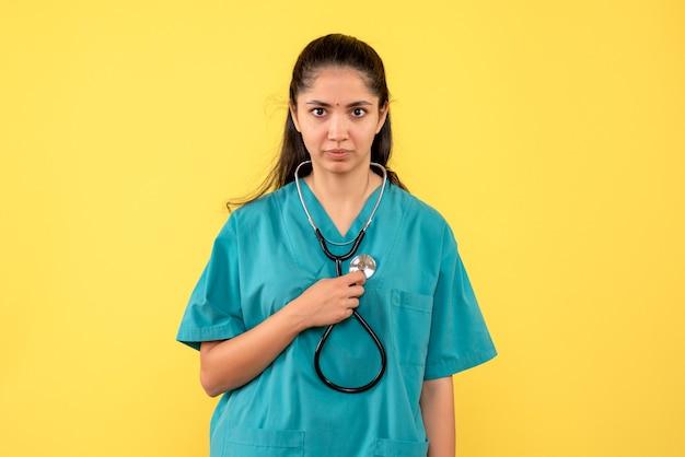 Medico femminile di vista frontale che tiene lo stetoscopio in posa