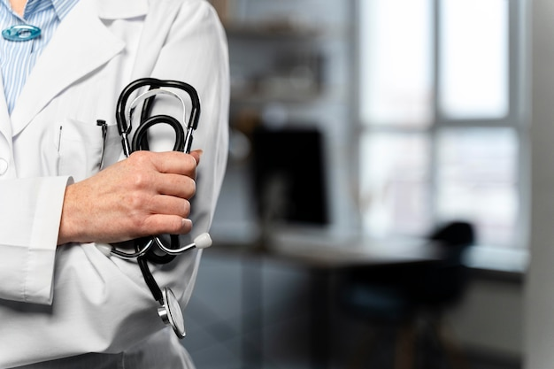 Front view of female doctor holding stethoscope with copy space