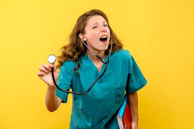 Stetoscopio femminile della tenuta del medico di vista frontale sullo spazio giallo