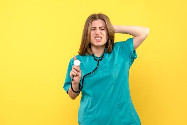 黄色の空間に眼圧計を保持している正面図の女性医師