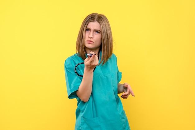 Medico femminile di vista frontale che tiene tonometro sullo spazio giallo