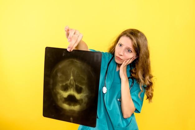 노란색 공간에 x- 레이 들고 전면보기 여성 의사