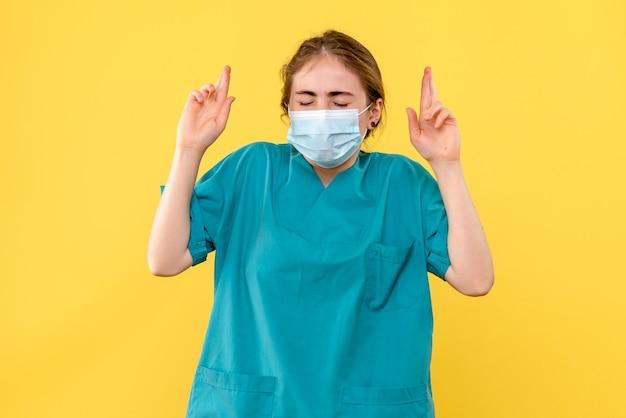 Medico femminile di vista frontale che spera nella maschera su pandemia dell'ospedale di salute del fondo giallo covid