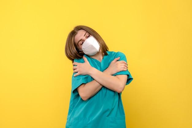 Medico femminile di vista frontale che si abbraccia sullo spazio giallo