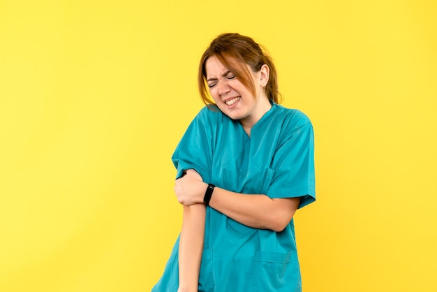 Front view female doctor hurt her hand on yellow space