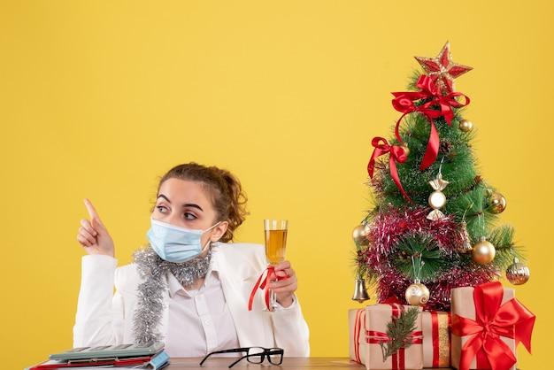 샴페인과 크리스마스를 축 하하는 마스크에 전면보기 여성 의사