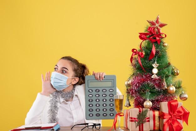電卓を保持しているマスクの正面図の女性医師