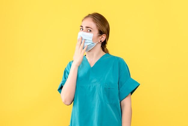 黄色の背景の健康パンデミックcovid-ウイルスのマスクで正面図の女性医師