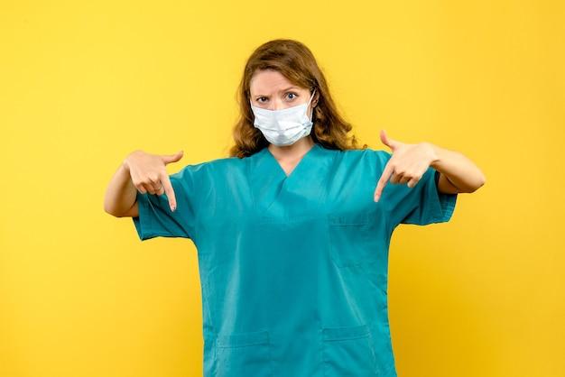 노란색 공간에 마스크에 전면보기 여성 의사