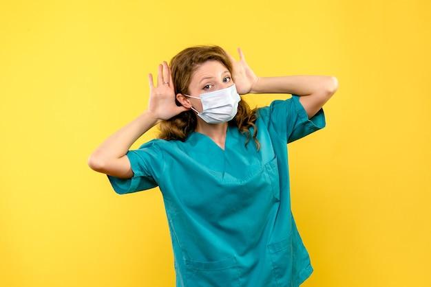 밝은 노란색 공간에 마스크에 전면보기 여성 의사