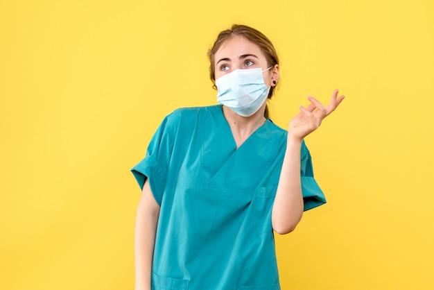 노란색 배경 건강 유행성 코로나 바이러스에 마스크에 전면보기 여성 의사