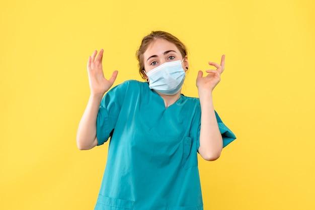 黄色の背景パンデミックcovid健康ウイルスのマスクで正面図の女性医師