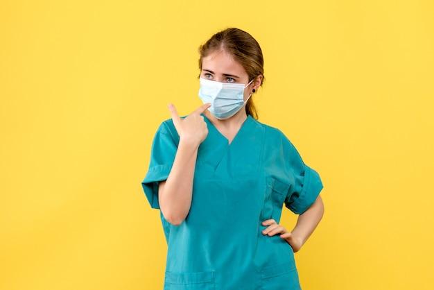 Вид спереди женщина-врач в маске на желтом фоне пандемический вирус здоровья covid