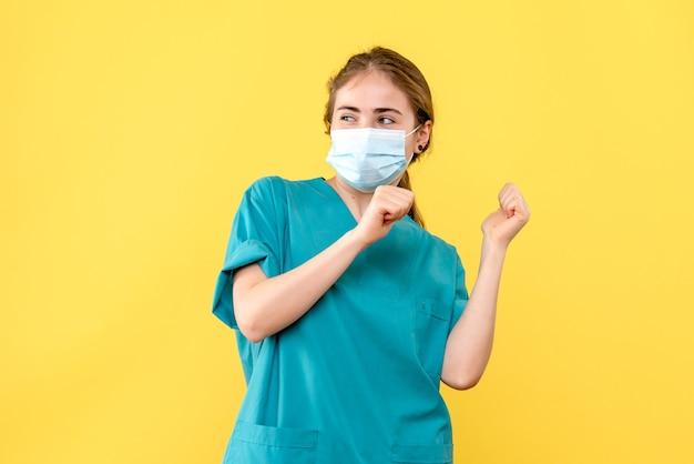 노란색 배경 건강 유행성 코로나 바이러스에 기뻐하는 마스크의 전면보기 여성 의사