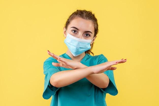 Вид спереди женщина-врач в медицинской рубашке и маске, пандемический вирус коронавируса covid-19 цвета здоровья