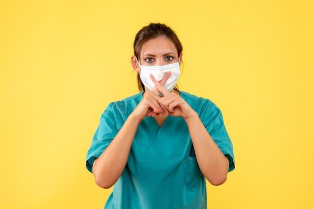 Вид спереди женщина-врач в медицинской рубашке и маске на желтом фоне