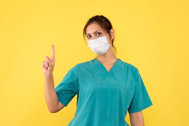 黄色の背景に医療シャツとマスクの正面図の女性医師