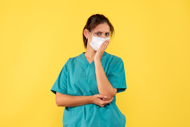 의료 셔츠와 노란색 배경에 마스크에 전면보기 여성 의사