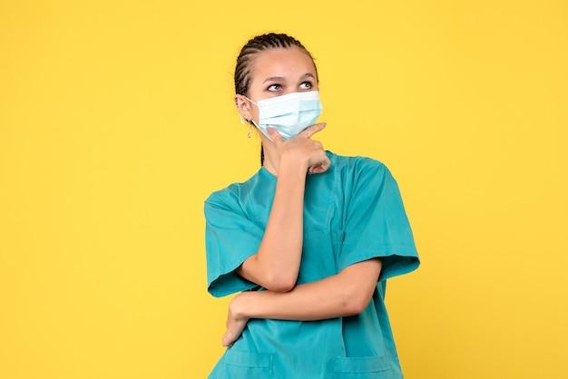 Вид спереди женщина-врач в медицинской рубашке и маске на желтом столе медсестра пандемической больницы вирус здоровья covid-