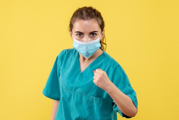 Вид спереди женщина-врач в медицинской рубашке и маске на желтом столе, единообразный цвет здоровья вируса, пандемия covid