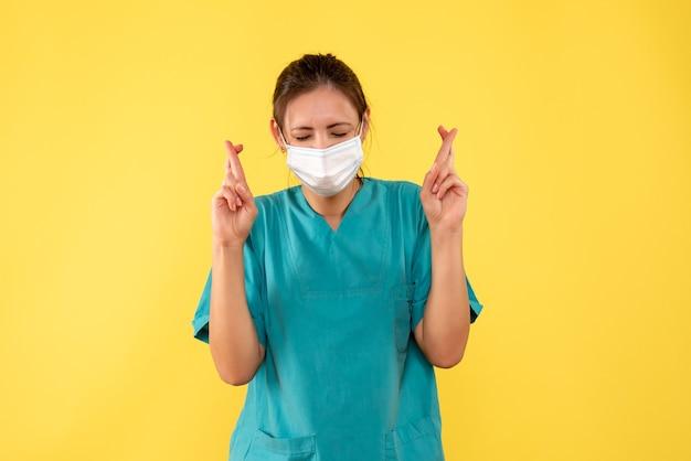 Вид спереди женщина-врач в медицинской рубашке и маске со скрещенными пальцами на желтом столе пандемическая больница цвет covid - вирус здоровья медик
