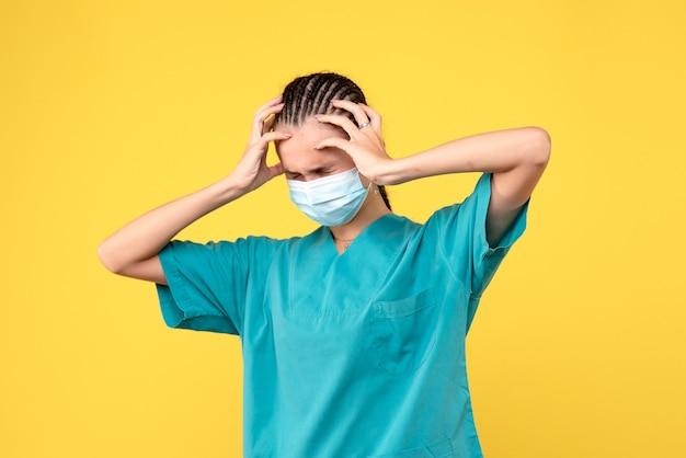 頭痛のある医療シャツとマスクの正面図の女性医師、ヘルスナースパンデミック病院covid-19メディック