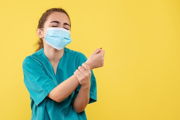 Вид спереди женщина-врач в медицинской рубашке и маске с поврежденной рукой, цветная форма вируса пандемии здоровья covid-19