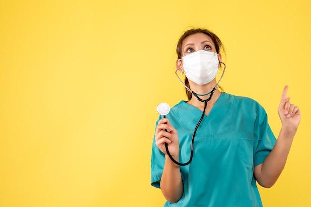 黄色の背景に聴診器と医療シャツとマスクの正面の女性医師