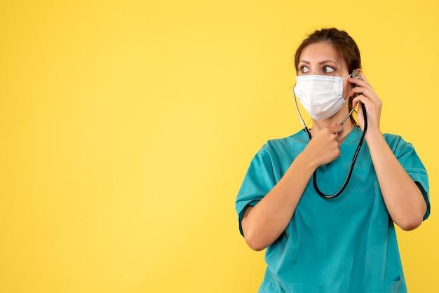의료 셔츠와 노란색 배경에 청진 마스크 전면보기 여성 의사