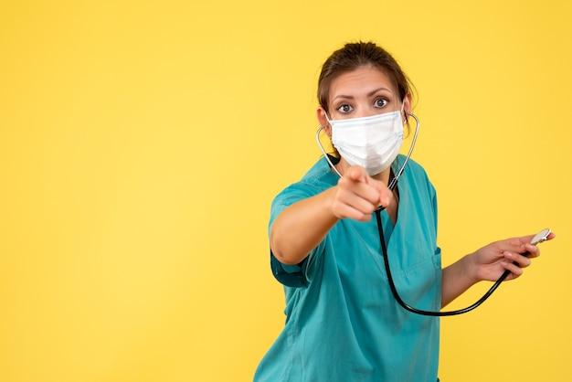 Вид спереди женщина-врач в медицинской рубашке и маске со стетоскопом на желтом фоне