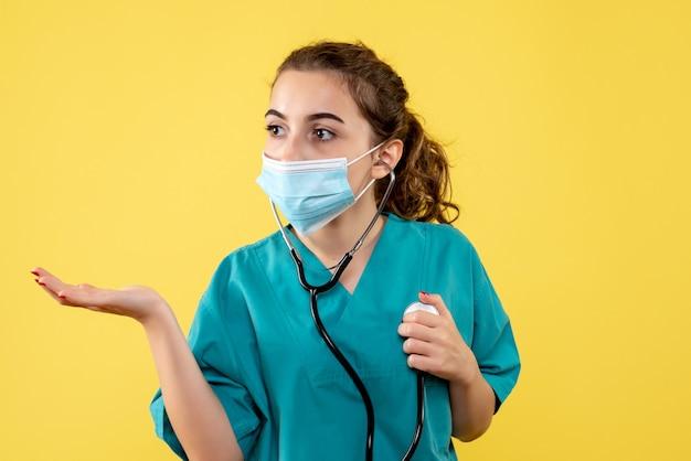Вид спереди женщина-врач в медицинской рубашке и маске со стетоскопом, вирусная однородная цветная эмоция, здоровье covid-19