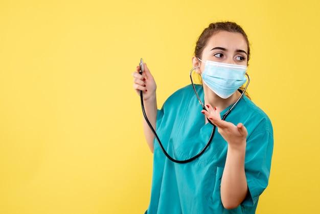 Вид спереди женщина-врач в медицинской рубашке и маске со стетоскопом, вирусная однородная цветная эмоция covid health