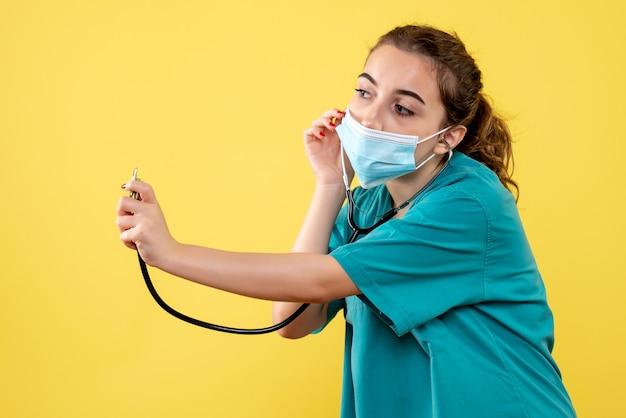 Вид спереди женщина-врач в медицинской рубашке и маске со стетоскопом, вирусная однородная цветная эмоция covid-