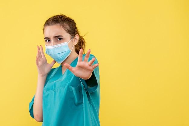 Вид спереди женщина-врач в медицинской рубашке и стерильной маске, пандемия вируса коронавируса