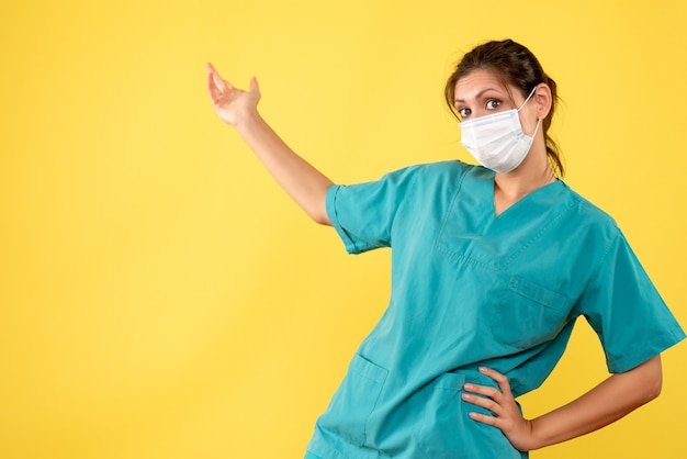 黄色の背景に医療シャツと滅菌マスクの正面図の女性医師