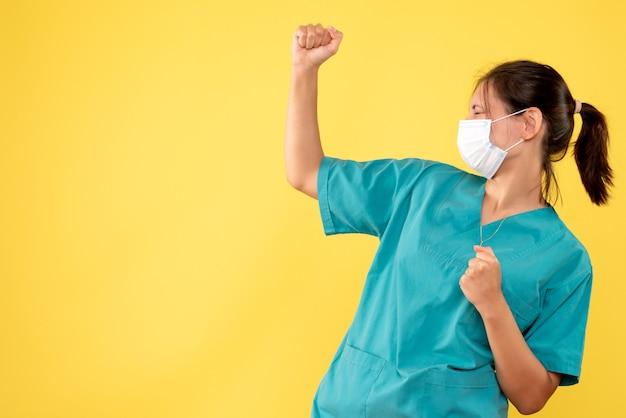 Вид спереди женщина-врач в медицинской рубашке и стерильной маске на желтом столе.