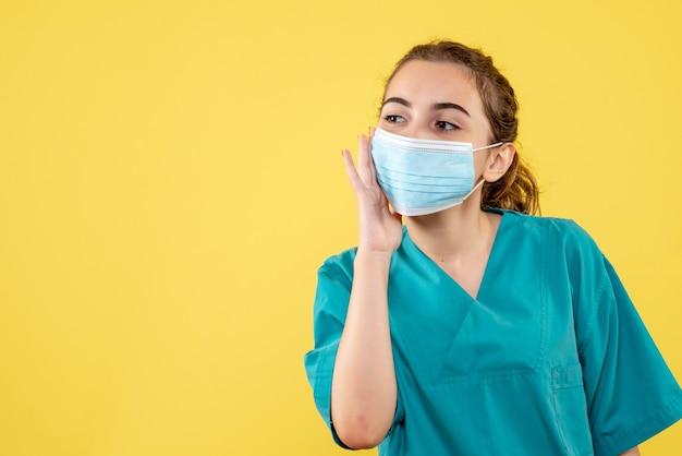 Вид спереди женщина-врач в медицинской рубашке и стерильной маске, вирусный однородный цвет covid-