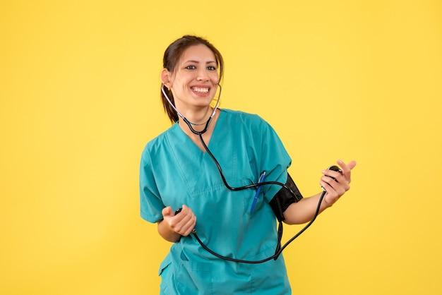 노란색 배경에 그녀의 압력을 검사하는 의료 셔츠에 전면보기 여성 의사