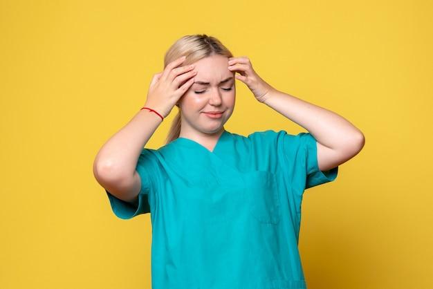 わずかな頭痛のある医療シャツを着た正面図の女性医師、パンデミックナースcovid-19感情メディック