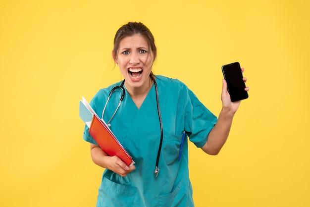 노란색 배경에 분석 및 전화를 들고 의료 셔츠에 전면보기 여성 의사
