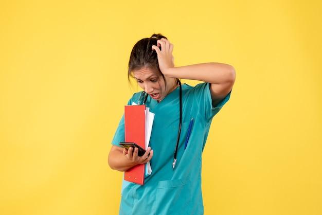 Вид спереди женщина-врач в медицинской рубашке, держащая анализ и телефон на желтом фоне