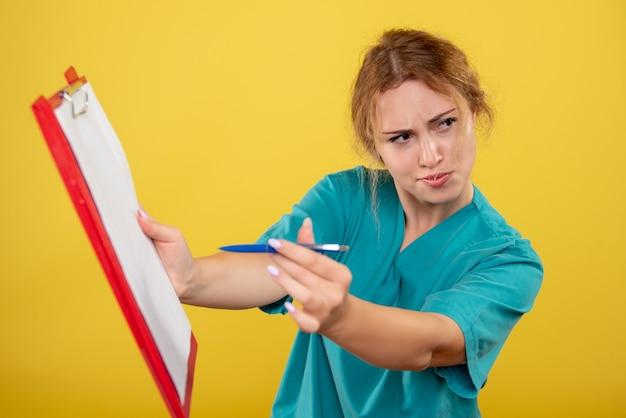 Вид спереди женщина-врач в медицинской рубашке, держащая анализ, эмоция цвета больницы covid-19