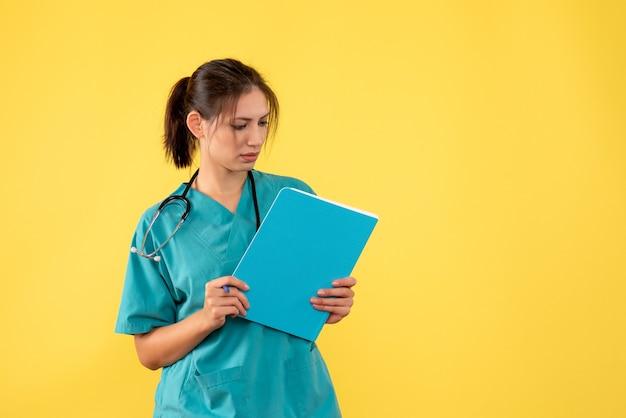 노란색 배경에 분석을 들고 의료 셔츠에 전면보기 여성 의사