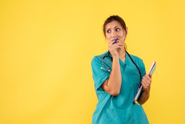Вид спереди женщина-врач в медицинской рубашке, держащая анализ на желтом столе, вирус здоровья, цвет covid- эмоциональная больница