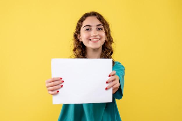 紙の分析、covid-19健康パンデミックウイルスの感情を保持している医療シャツの正面の女性医師