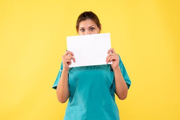 黄色の背景に紙の分析を保持している医療シャツの正面の女性医師