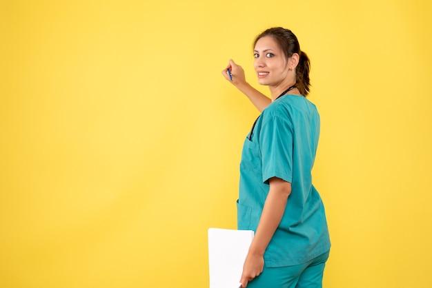 노란색 배경에 종이 분석을 들고 의료 셔츠에 전면보기 여성 의사