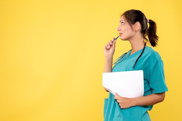 Вид спереди женщина-врач в медицинской рубашке, держащая анализ бумаги на желтом фоне Бесплатные Фотографии